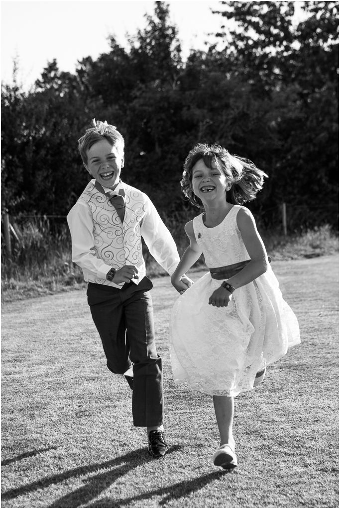wedding photographer hertfordshire natural photo of bridesmaid and pageboy having fun